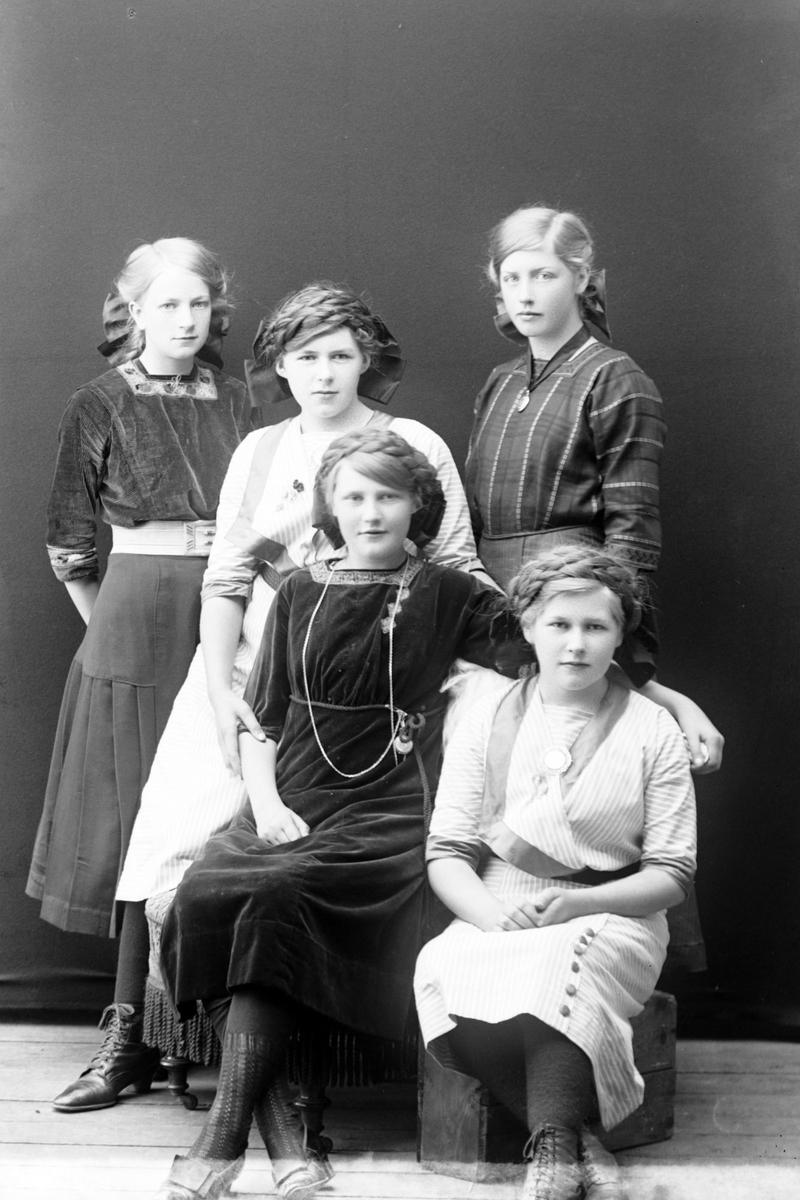Studioportrett av fem piker, alle med sløyfer i håret.
