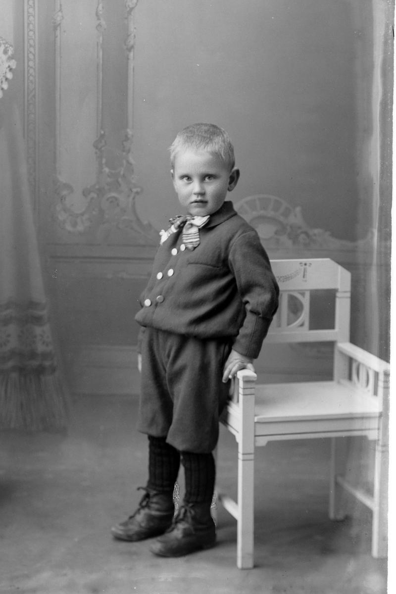 Studioportrett av en liten gutt som står ved siden av en stol.