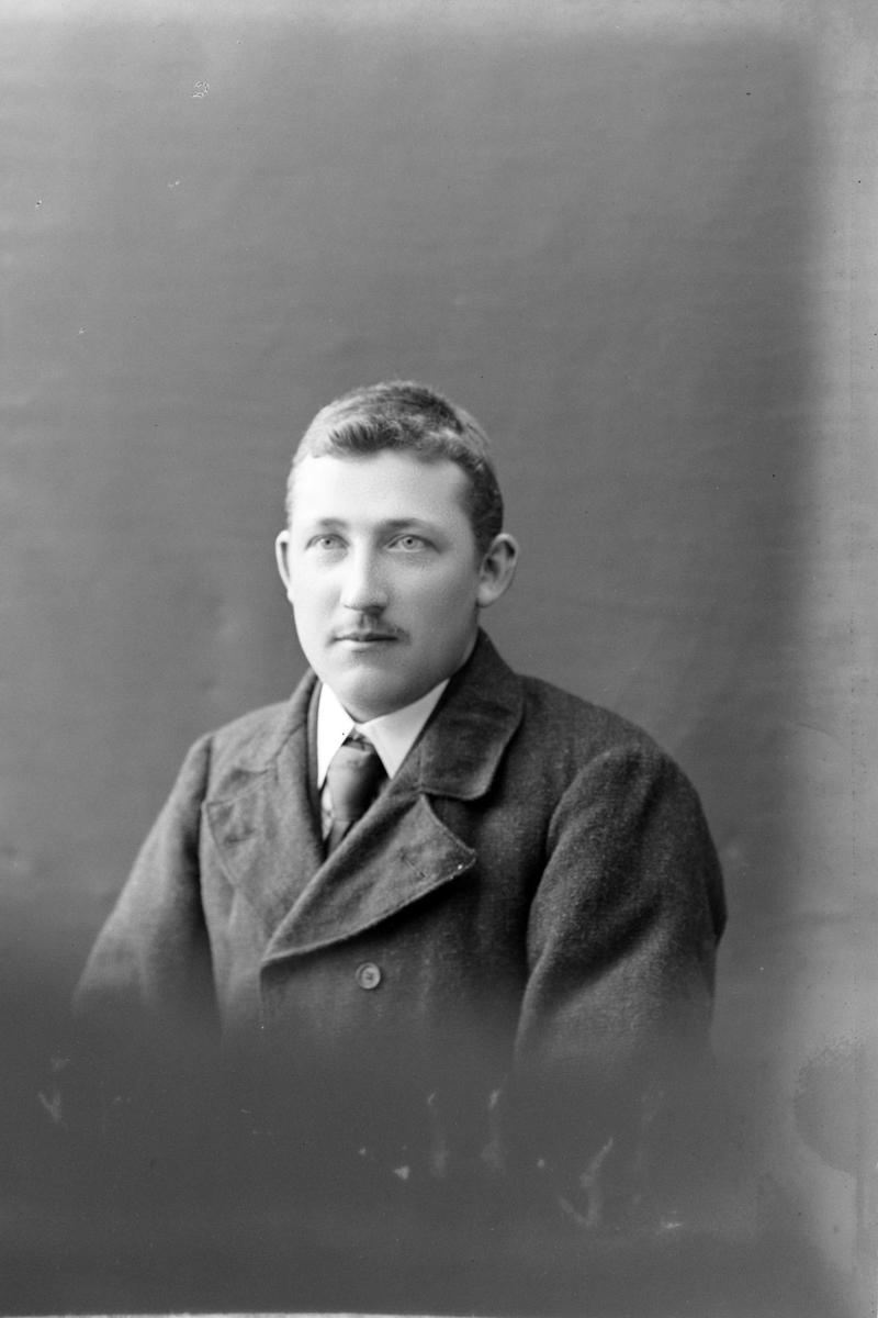 Studioportrett av en mann i halvfigur, muligens Elias Nikolai Madsen.