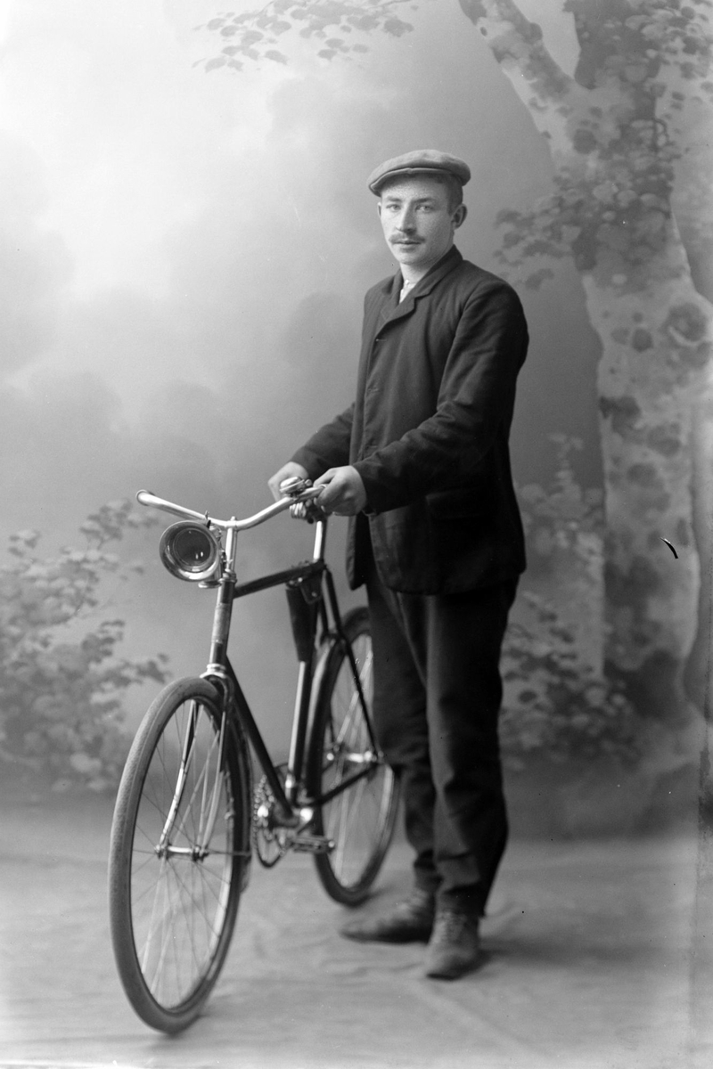 Studioportrett av en mann med sykkel i helfigur.