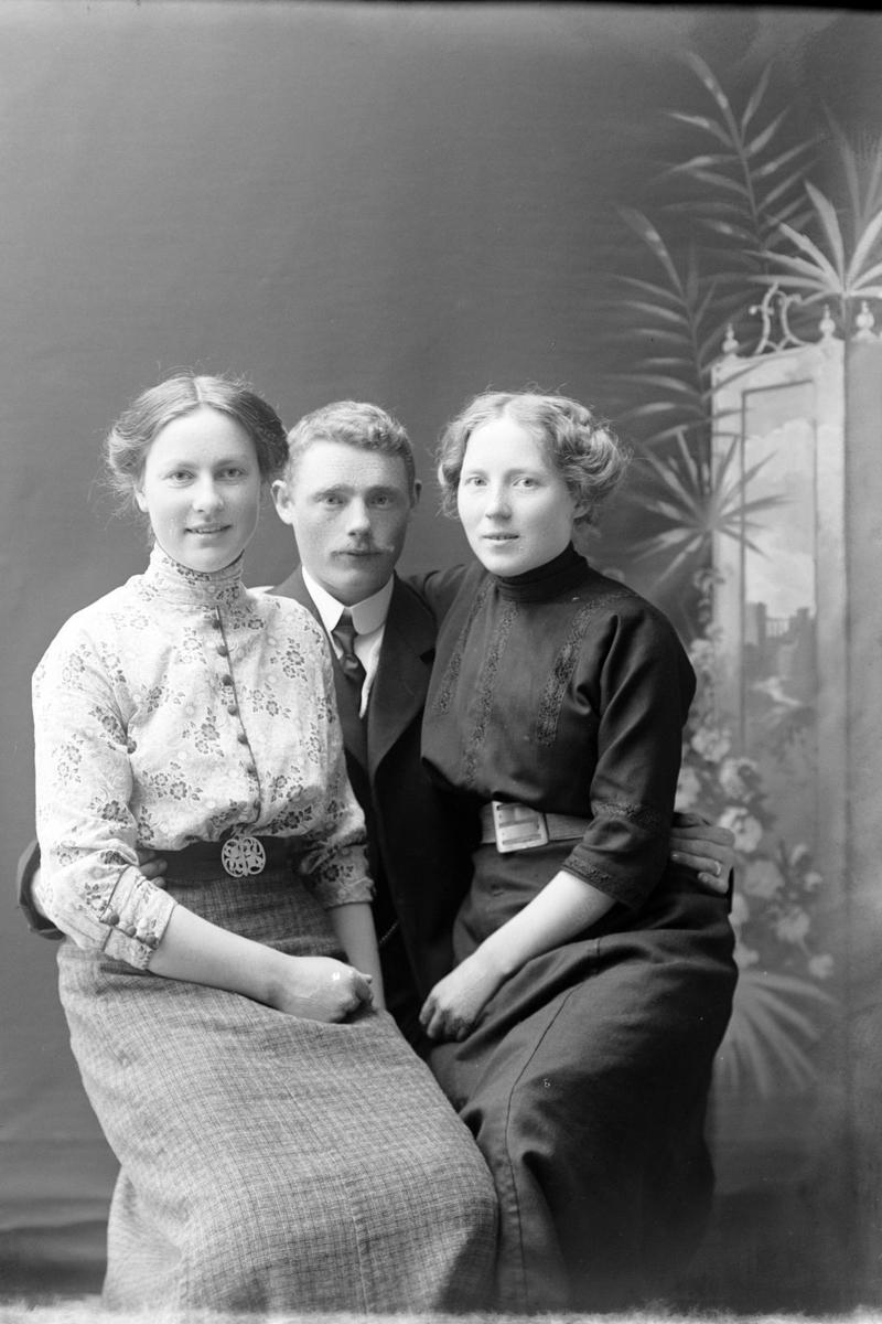 Studioportrett av to kvinner som sitter på en manns fang.