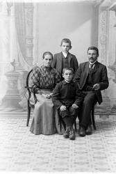 Gruppeportrett av sittende par med to barn, tatt i fotoateli
