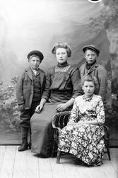 Studioportrett av en ung kvinne og tre barn.