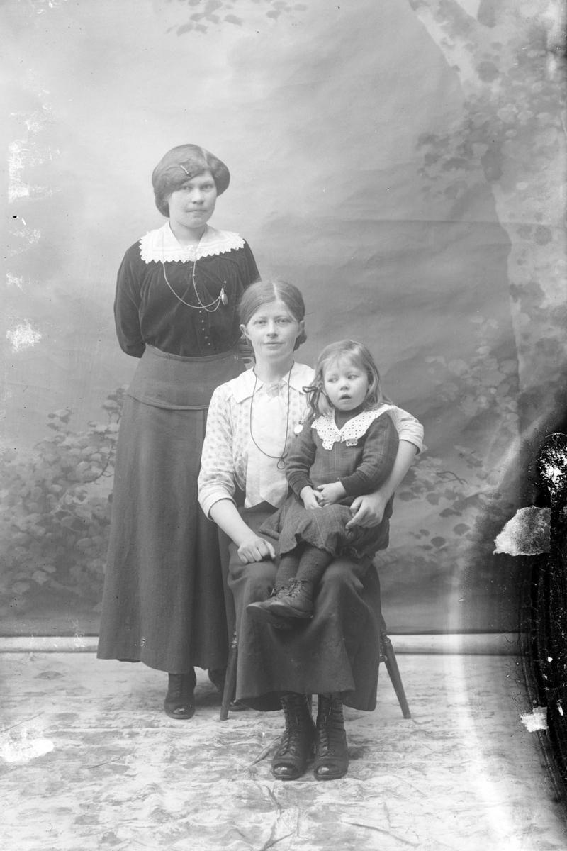Studioportrett av to kvinner med en liten jente.