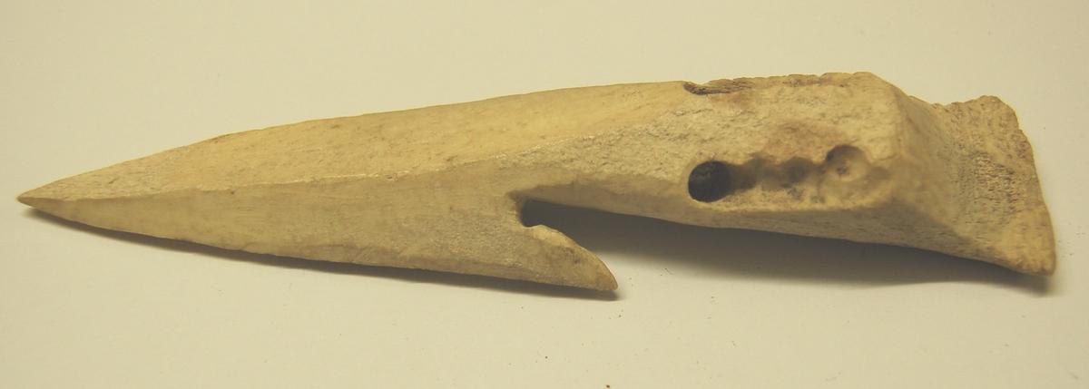 Gjenstanden er utskoren av kvalbein og formet som en spydspiss med en mothake (agnhald). Nederst på spydspissen er der laget hull til festing av linen.