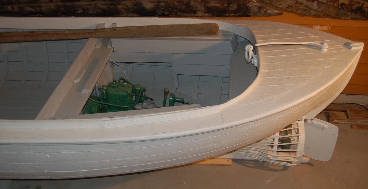 """Snekkeliknande kravellbygd trebåt med eikespant, utstyrt med bensinmotor og årer til framdrift. Til beskyttelse av propellen mot skader fra isklumper, er den omgitt av en """"korg"""" av rundtjern."""