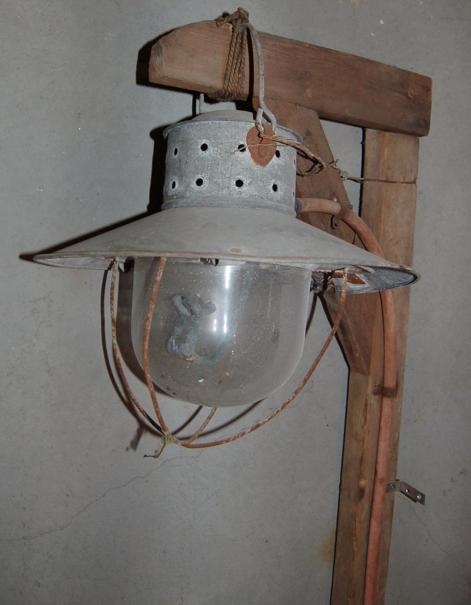 Lysarmatur av blekk med kuppel av glas, festet til en vel to meter lang trestang. Lyskilden bestod av en gass/karbidbrenner inne i glaskuppelen, med tilførsel av gass gjennom en gummislange fra en karbidbeholder som stod ved foten av stanga.