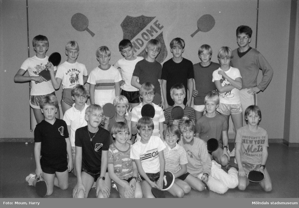 """Bordtennis i Almåsskolans sporthall i Lindome, år 1984. """"Tränare Roger Brundin längst till höger ser till att grabbar och flickor lär sig spelet på rätt sätt.""""  För mer information om bilden se under tilläggsinformation."""