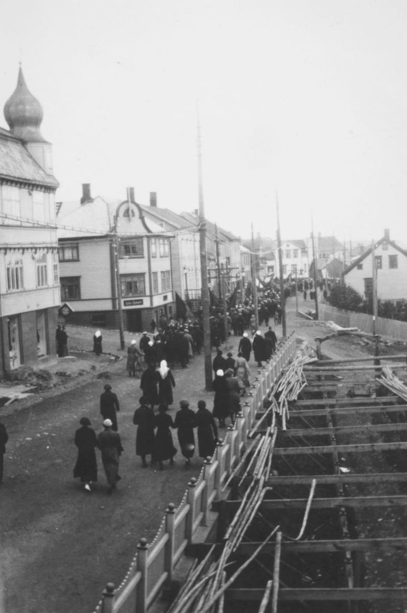 Mange mennesker som går bortover en gate, muligens 17.mai i Vadsø? Alle er mørkkledte. Et av husene som ligger på øversiden av veien har en kuppel på taket. I tekst til bildet står det at det er tatt i mai, i slutten av tredveårene