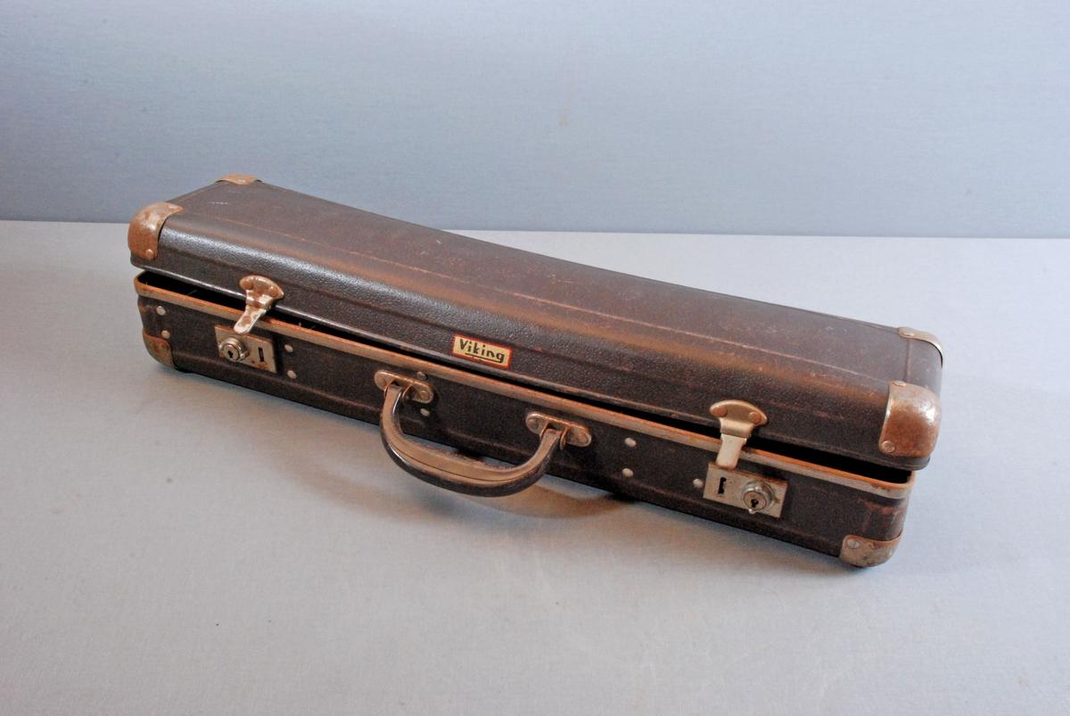 Koffert med plass for de enkelte delene; strålerør festet med to lærreimer, papp skillevegger for manometre og strålerørmunnstykke. Et munnstykke ligger løst i kofferten. Kofferten har metallbeslag i hjørnene, to knepplåser og bærehåndtak.
