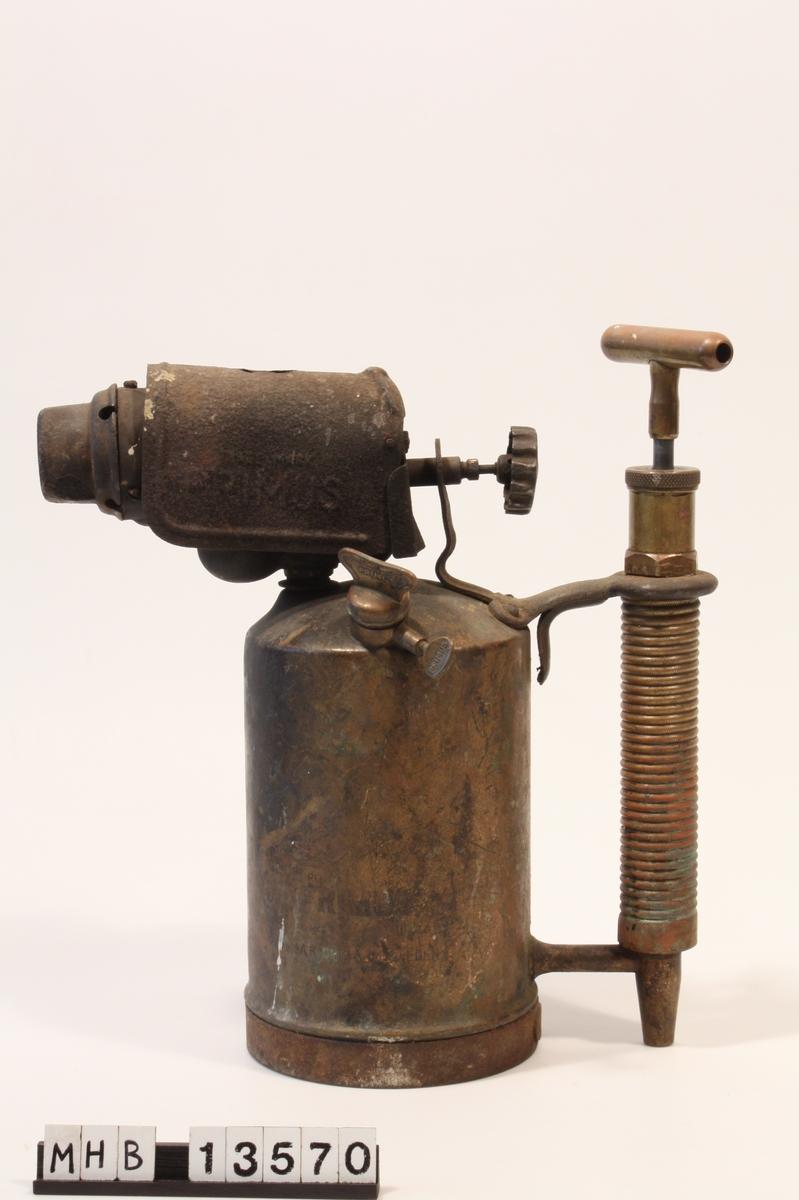 Blåselampe med tank med toppfylling, luftpumpe frittstående som håndtak. Flammedelen med hette er montert på toppen av tanken. Tekst preget i tanken og på hetten.