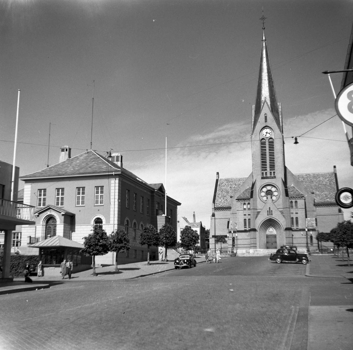 Gateparti med  Vår Frelsers kirke midt imot. Til v. for kirken, litt lenger ned i bakken, ligger Posthuset. Noen biler i gata, og flere mennesker på fortau og i gata. Vår Frelsers kirke ( bygget 1901) og Posthuset (bygget 1929). Bildet er tatt fra fortauet ved Nils Sund A/S (Haraldsgt. 159).