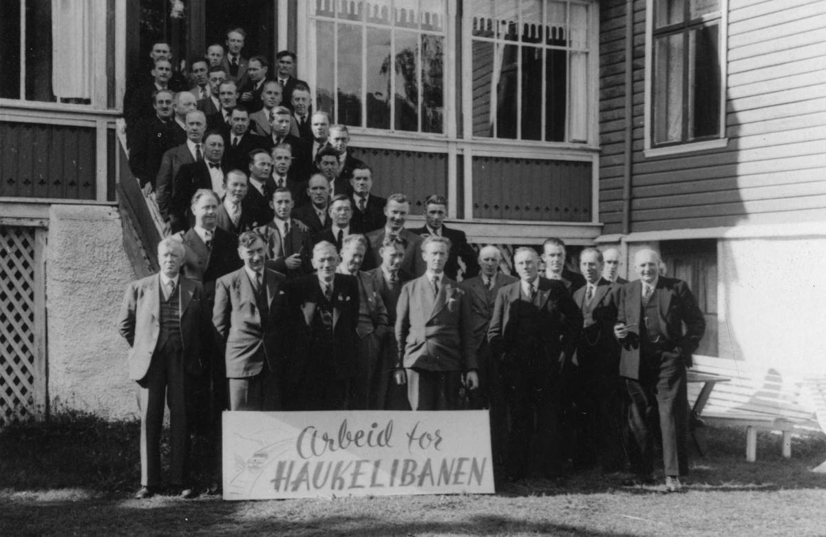 """Breifonn hotell 1946. Det store Haukelibanemøtet. Flere menn oppstilt i trappa og foran trappa til Breifonn hotell. Foran mennene en stor plakat der det står : """" Arbeid for Haukelibanen """"."""