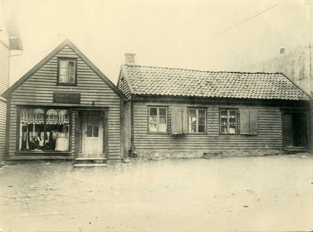 To hus, det ene med gavlen mot og det andre med langsiden mot gata. Huset til v. har skilt med: Kaia Hauge, broderiforretning. Disse to små husene stod på tomten Strandgt. 172 ,hvor Torvastad og Skåre Sparebank i 1910 bygget sitt nye hus. Bildet er fra omkring 1908. Kaia Hauge hadde da en liten moteforretning i huset til v. I det andre var det øl- og vinutsalg.
