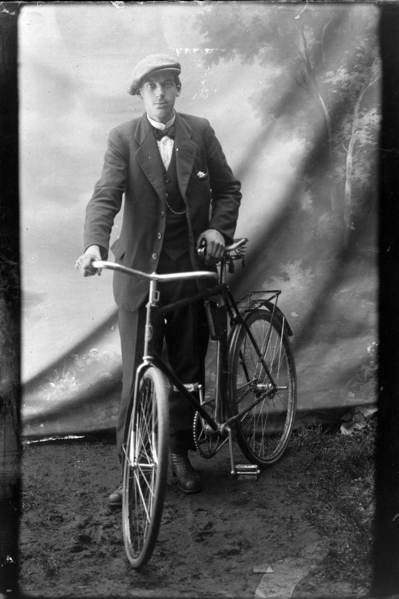 Studioportrett i helfigur av en mann med sykkel.
