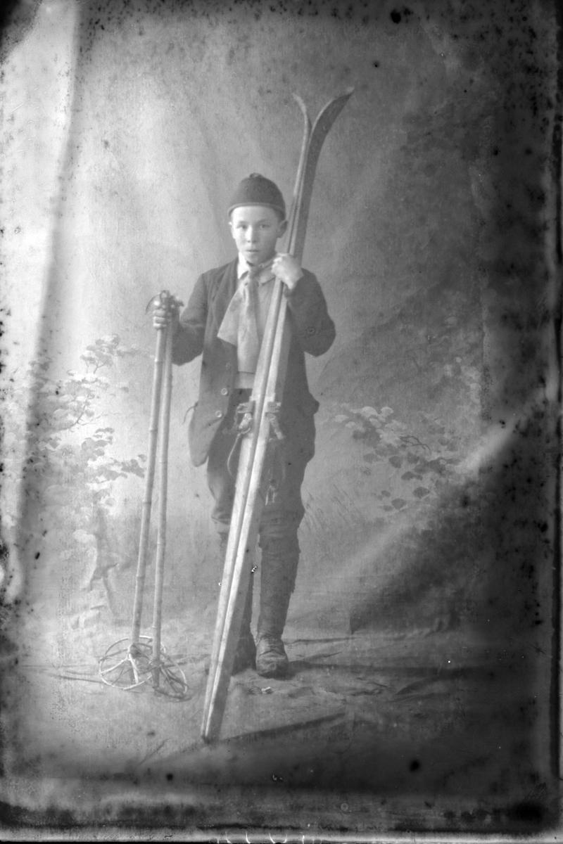 Studioportrett av en gutt med ski og skistaver.