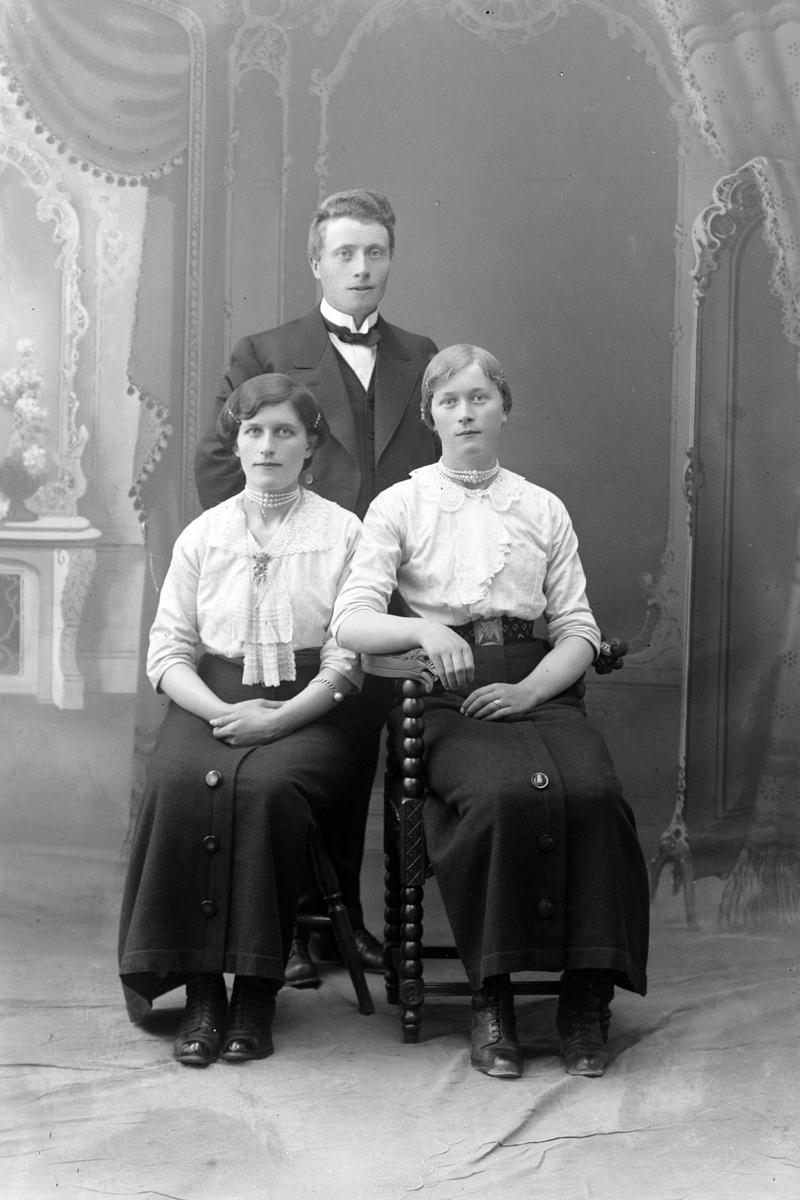 Studioportrett av en mann stående bak to kvinner som sitter.