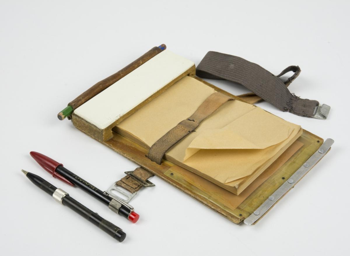 Knäblock med fäste för anteckningsblock. Läderhylsor för pennor. Plastskiva på baksidan. Blocket fästes runt benet med ett resårband.