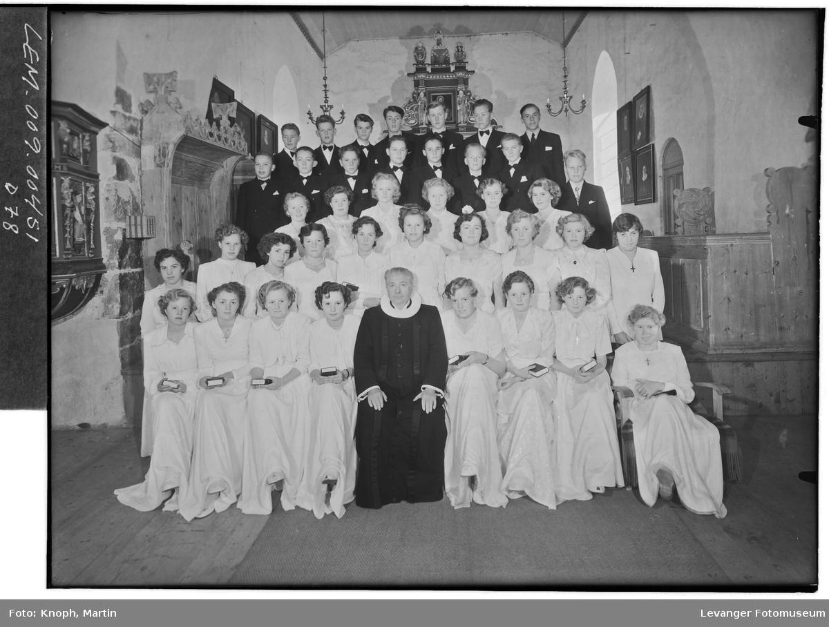 Konfirmanter med prest i kirka