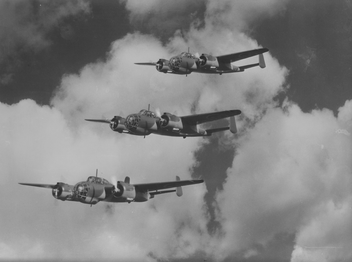 Tre flygplan B 18A i formationsflygning i luften.