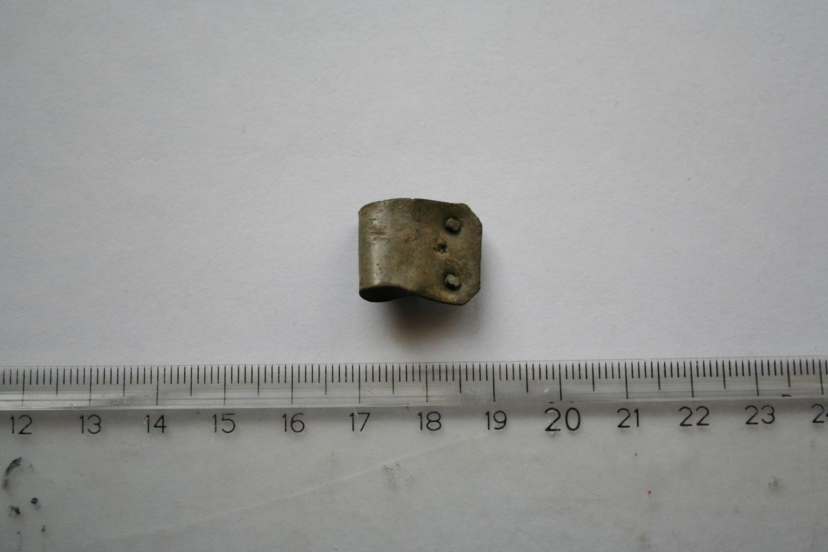 Rektangulært beslag som er bøyd. hjørnene er skrådd. Den ene enden er brukket av. To naglehull bevart på ene enden med nagler sittende i. Det er spor etter et tilsvarende naglehull i den avbrukkede enden.  Beslaget er laget av en tynn plate av kobberlegering. Trolig er dette skrapmetall som er ment å smeltes om.