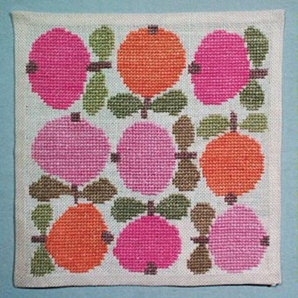 Använd som broderimodell i hemslöjdsbutiken - Kalmar läns Hemslöjd. Duk med äpplen åt olika håll över hela ytan. Broderade med korsstygn i rosa, grönt och gråbrunt.