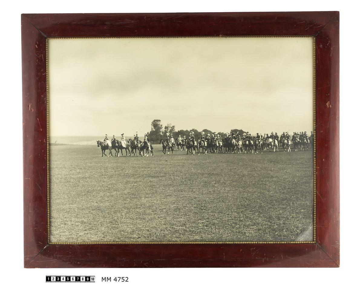 Fotografi av kungliga personer och officerare i uniformer till häst. Fotografiet är taget i Tyskland vid parad av Preussischen Fusilier Regemente. Bland de kungliga märks kejsar Wilhelm II, drottning Victoria och kung Gustav V av Sverige. Inom glas och ram av polerad mahogny.