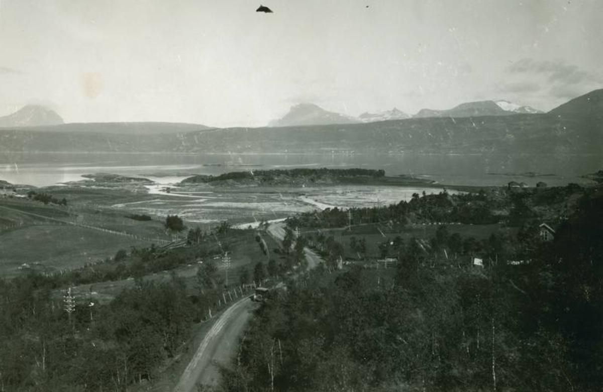Seines. Veien mot Seines. Utsikt mot Herjangen, Trollvik. Bil på veien. Skogøya i midten. Stor leire. Innmarka tilhører Markusson-eiendommen