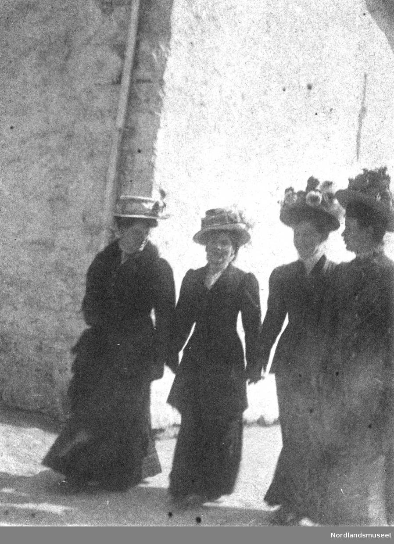 Gruppebilde. 4 kvinner med blomsterhatter og sorte kjoler foran steinbygning.