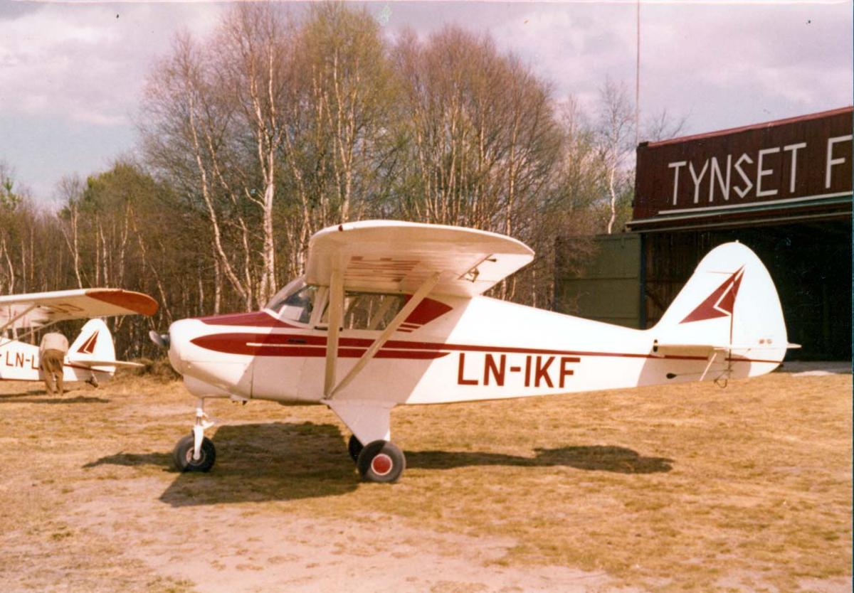 """1 fly på bakken, Piper Colt PA-22 LN-IKF. I bakgrunnen bygning med skilt - påskrift """"Tynset flyklubb"""