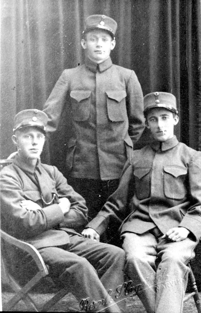 Gruppebilde. 3 personer, menn i militæruniform. Innendørs