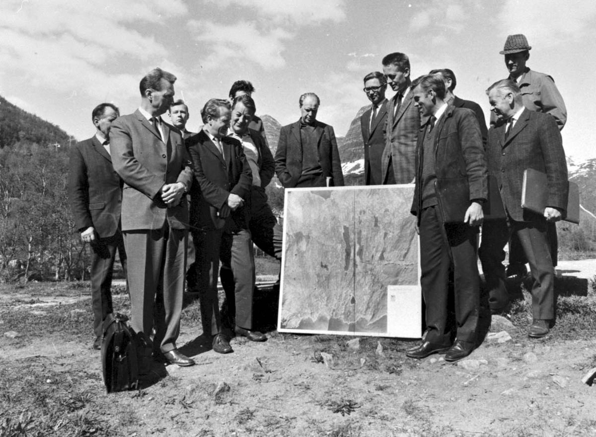 Gruppebilde. Flere personer, menn, med kart (foto) mellom seg.