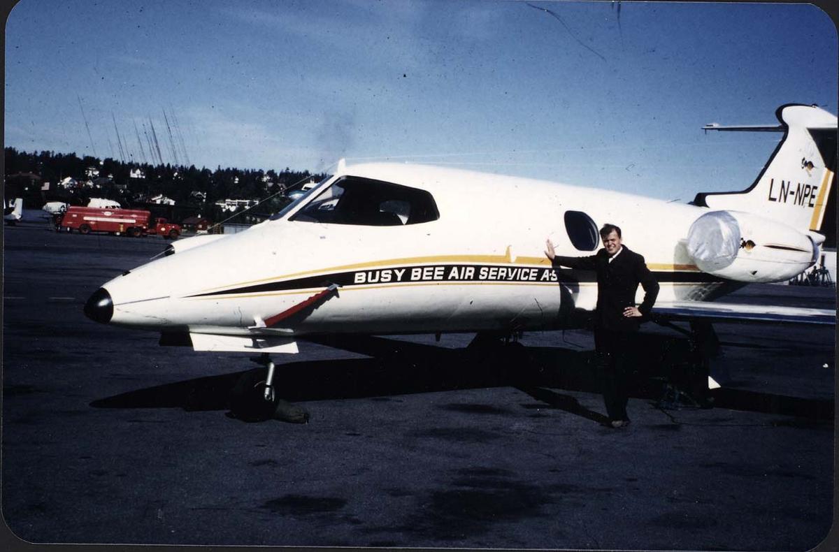 Lufthavn. 1 fly på bakken Lear Jet Model 23 LN-NPE fra Busy Bee. Portrett, 1 person ved flyet.
