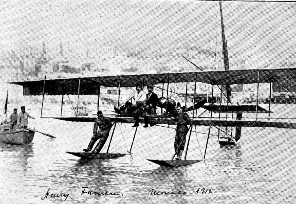 Ett fly på vannet, Henry Farman. Fire personer, menn, på flyet. Åpen båt (tilbringerbåt) med to personer ombord ved flyet.