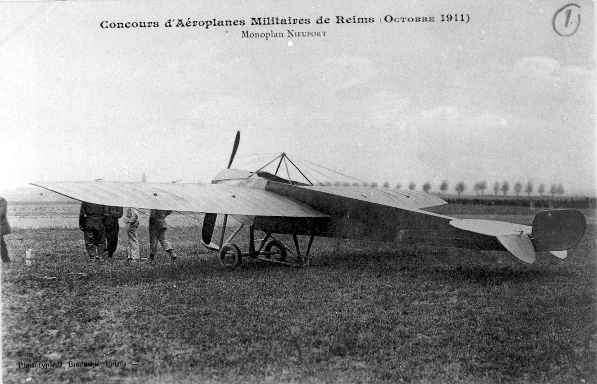 Ett fly på bakken, Nieuport. Noen personer ved flyet.