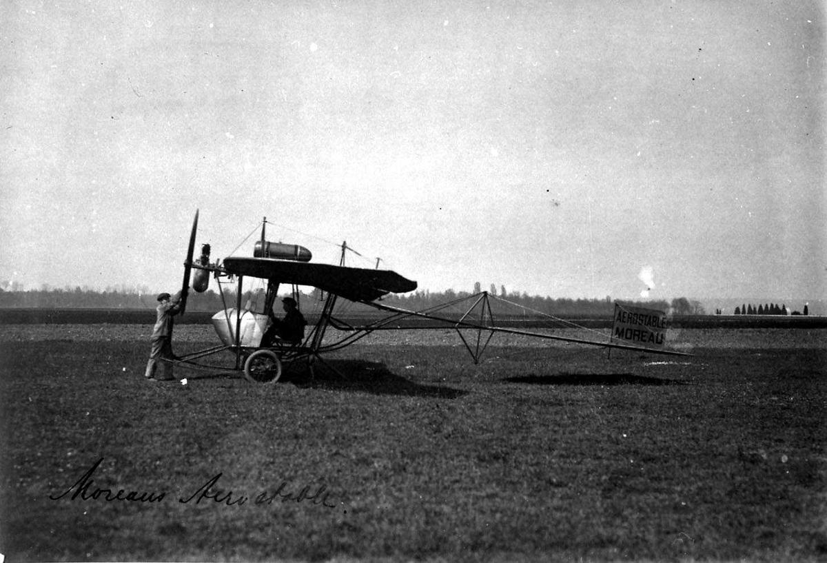 Ett fly på bakken, Moreau. To personer, menn, ved flyet.