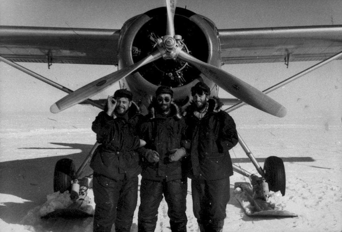 Tre personer foran ett fly, Otter. Snø på bakken.