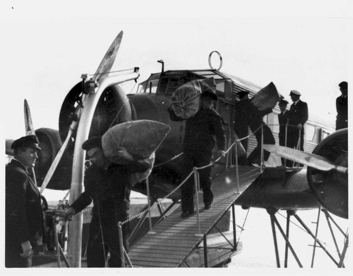 Ett fly på havet. Junkers Ju52. Flere personer med sekker ved flyet.
