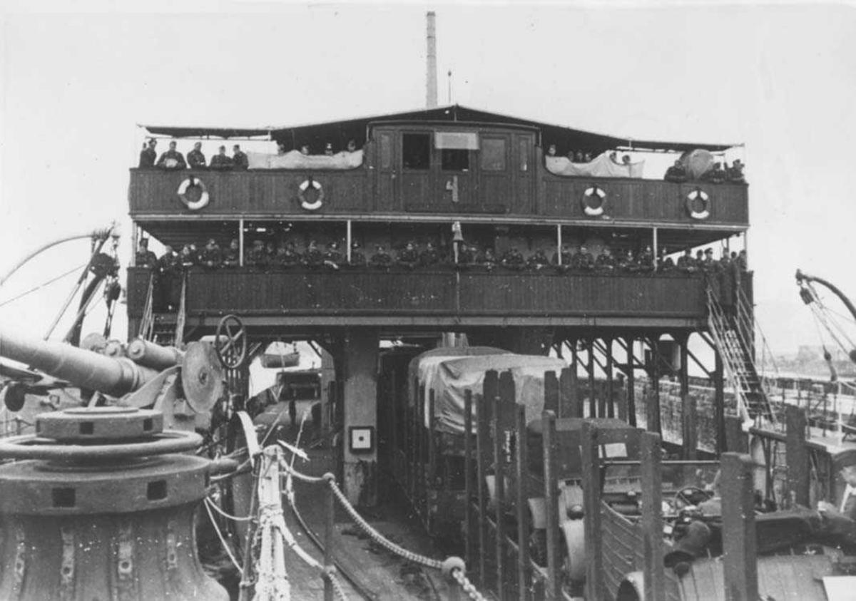 En båt lastet med jernbanevogner fulle av militærkjøretøyer. Militære mannskaper på båten.