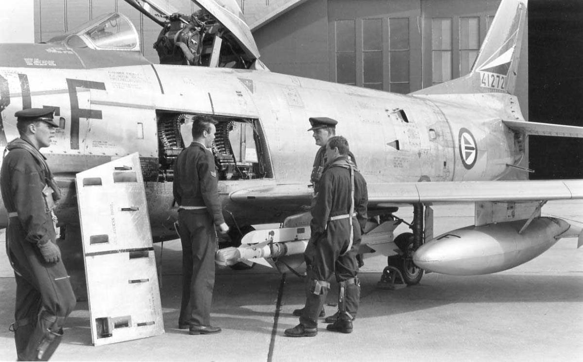Fire personer samlet utenfor et jagerfly.