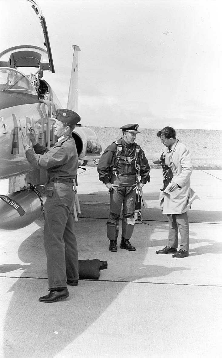 Tre personer ved siden av et jagerfly.