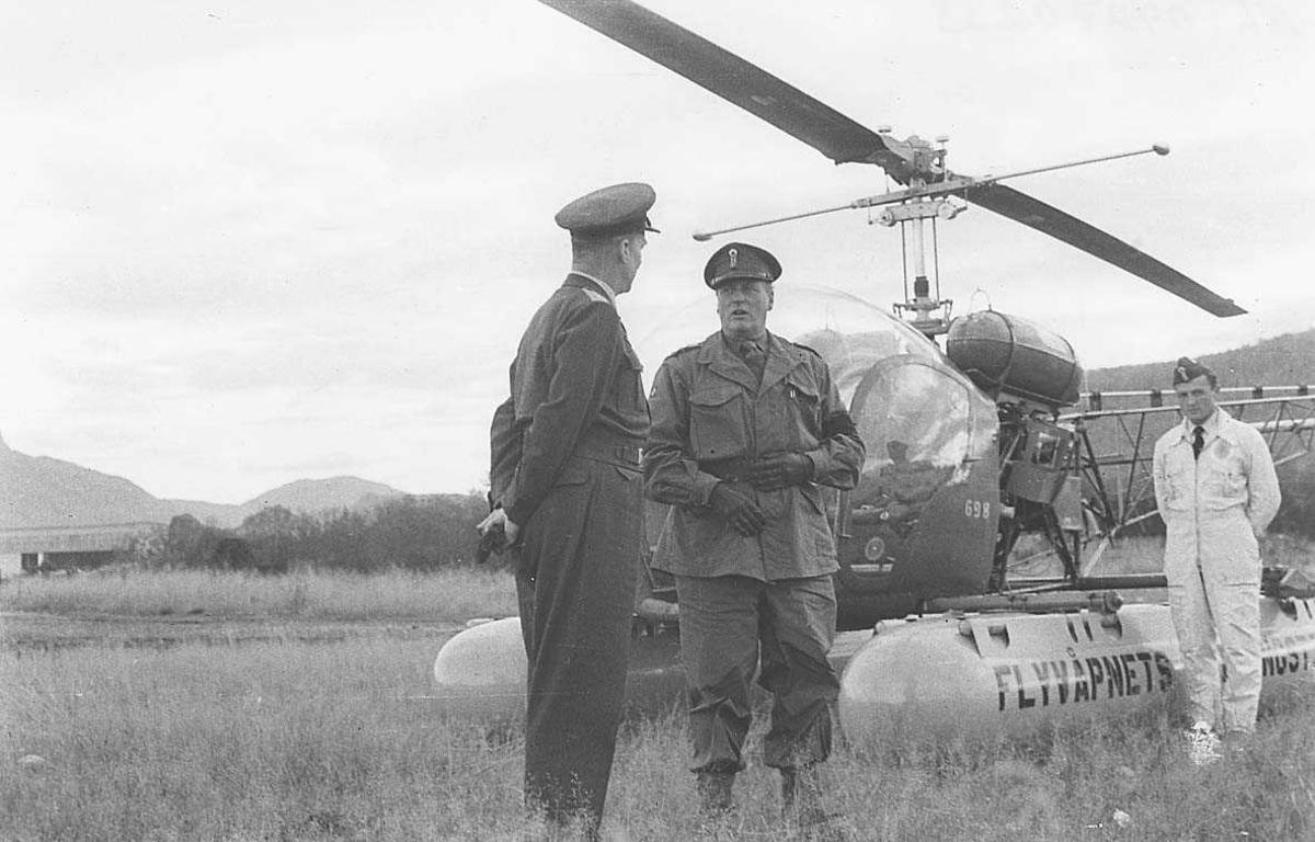 2 offiserer i samtale Kong Olav og Odd Bull 1 person i bakgrunnen ved siden av et helikopter.
