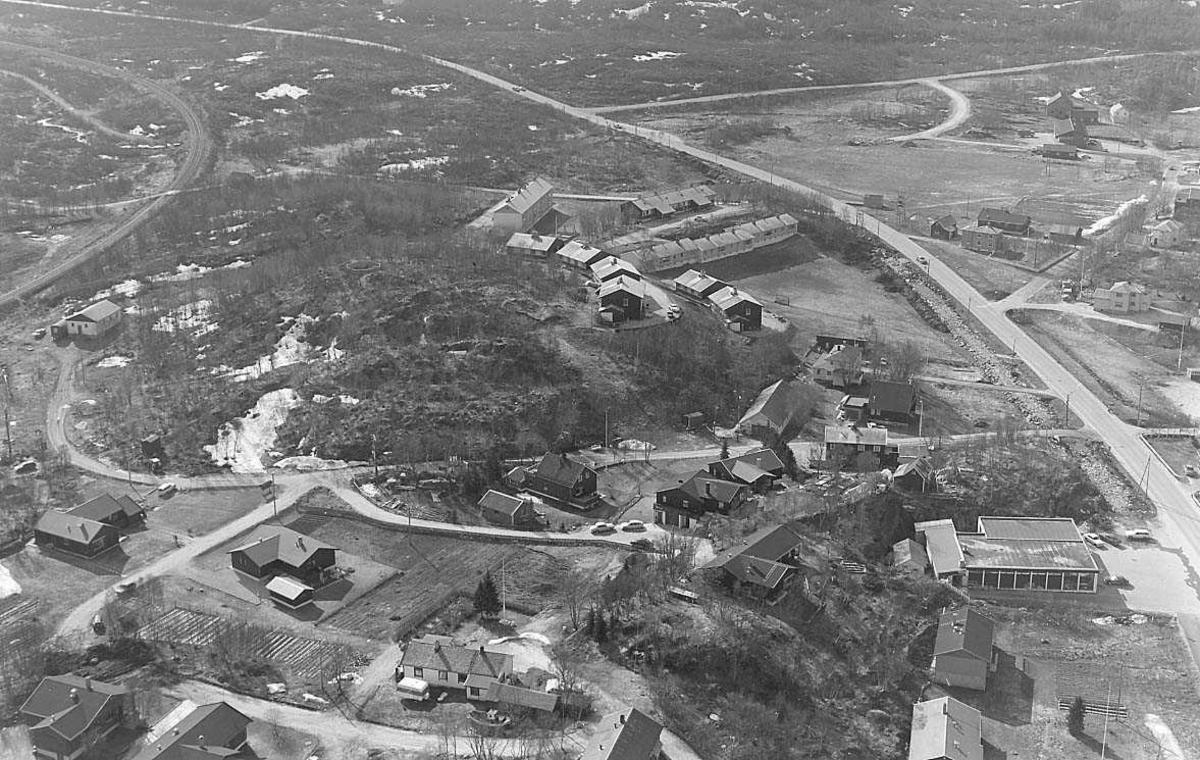 Bebyggelse med skog, veier og jernbanelinje.