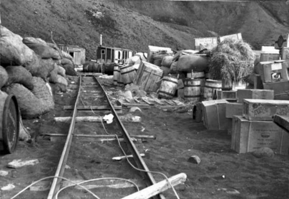 Jernbanespor og masse tønner og annet utstyr. Bygninger bak.