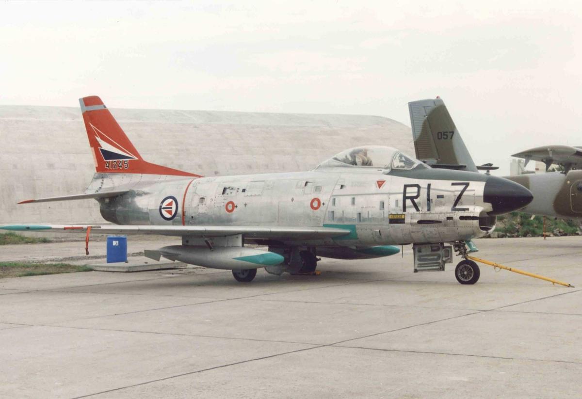 Lufthavn. Ett fly på bakken, F-86K  Sabre  RI-Z ser 54-1245. Bak står DHC-6 Twin Otter 057.