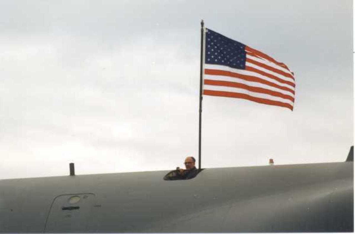 Lufthavn (flyplass) Ett fly på bakken. Cockpiten av C-5 galaxy fra U.S. Air Force utvendig med Amerikansk flagg. En person på flyet.