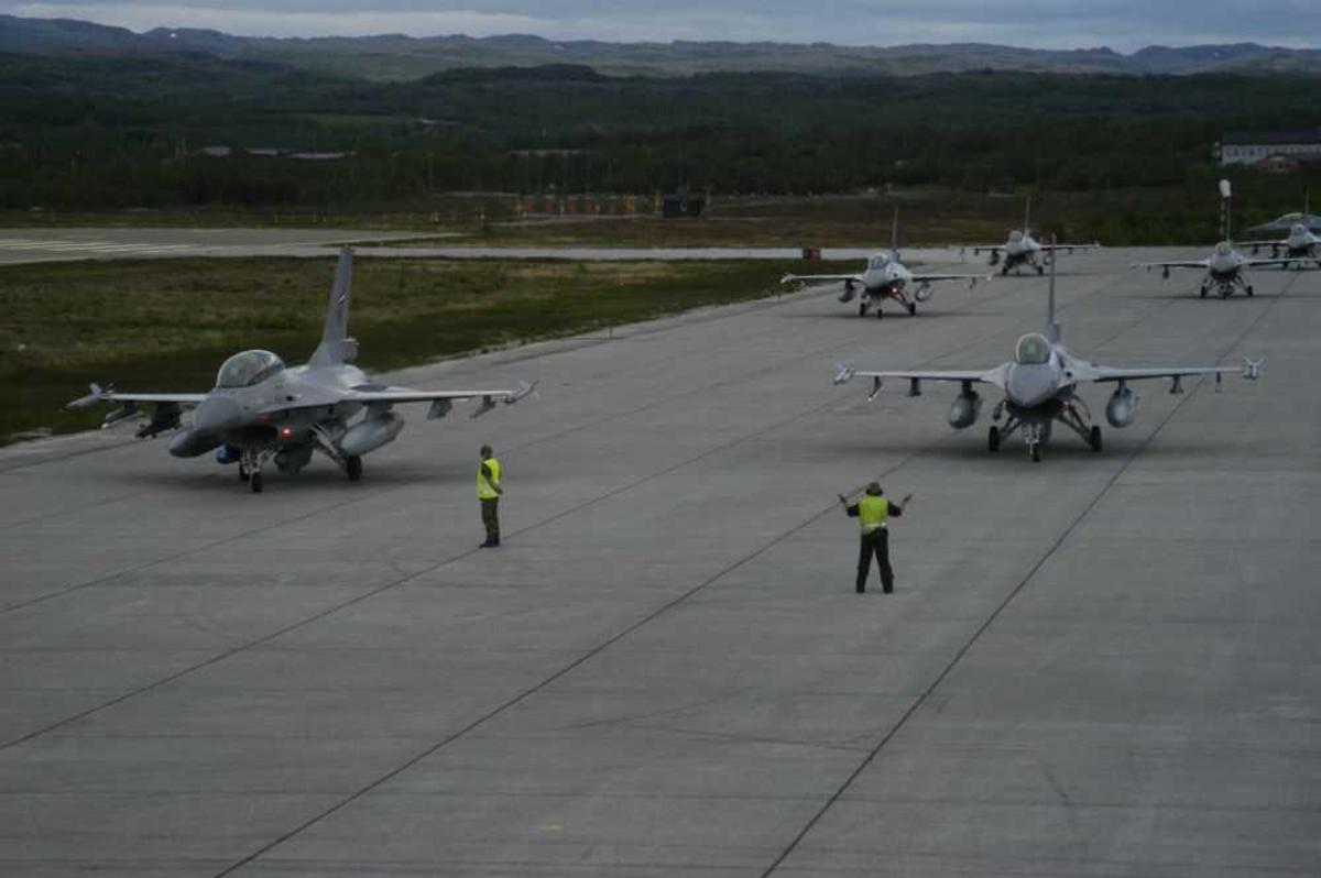 Lufthavn (flyplass). Flere fly på bakken F-16. To personer dirigerer flyene.