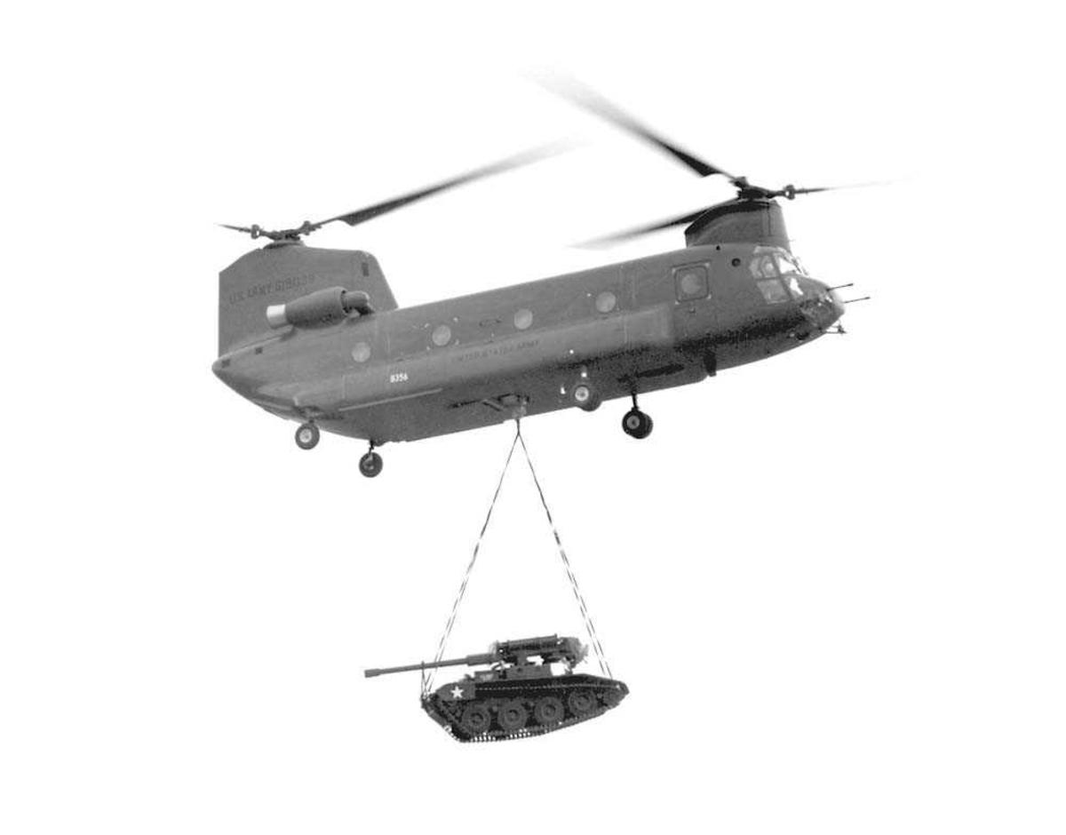 1 helikopter i luften. Boeing Chinook CH-47B. Har en tanks hendende under seg.