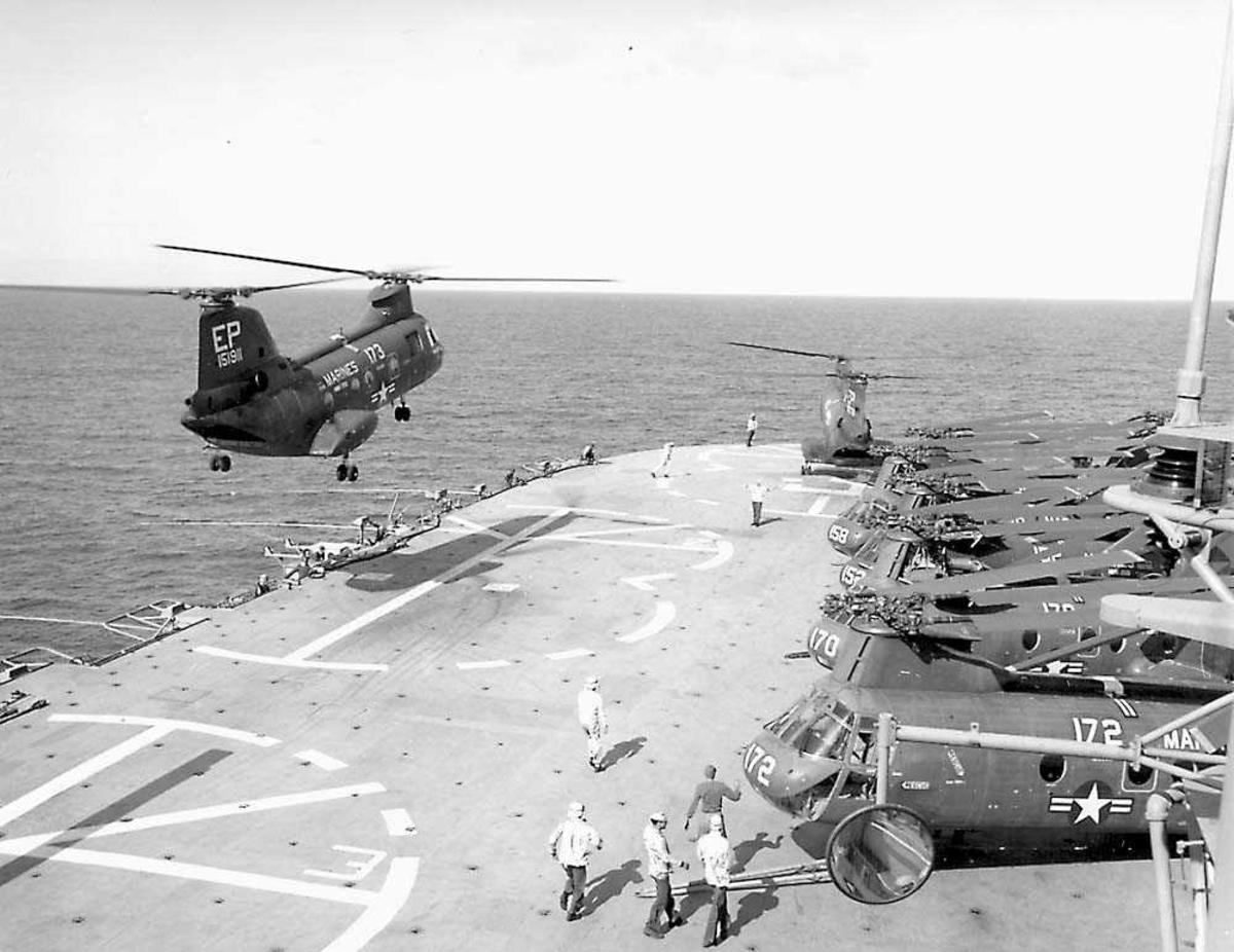 1 helikopter i luften over et hangardekk. Boeing Vertol CH-46 Sea Knight Flere helikoptere og personer på dekk.