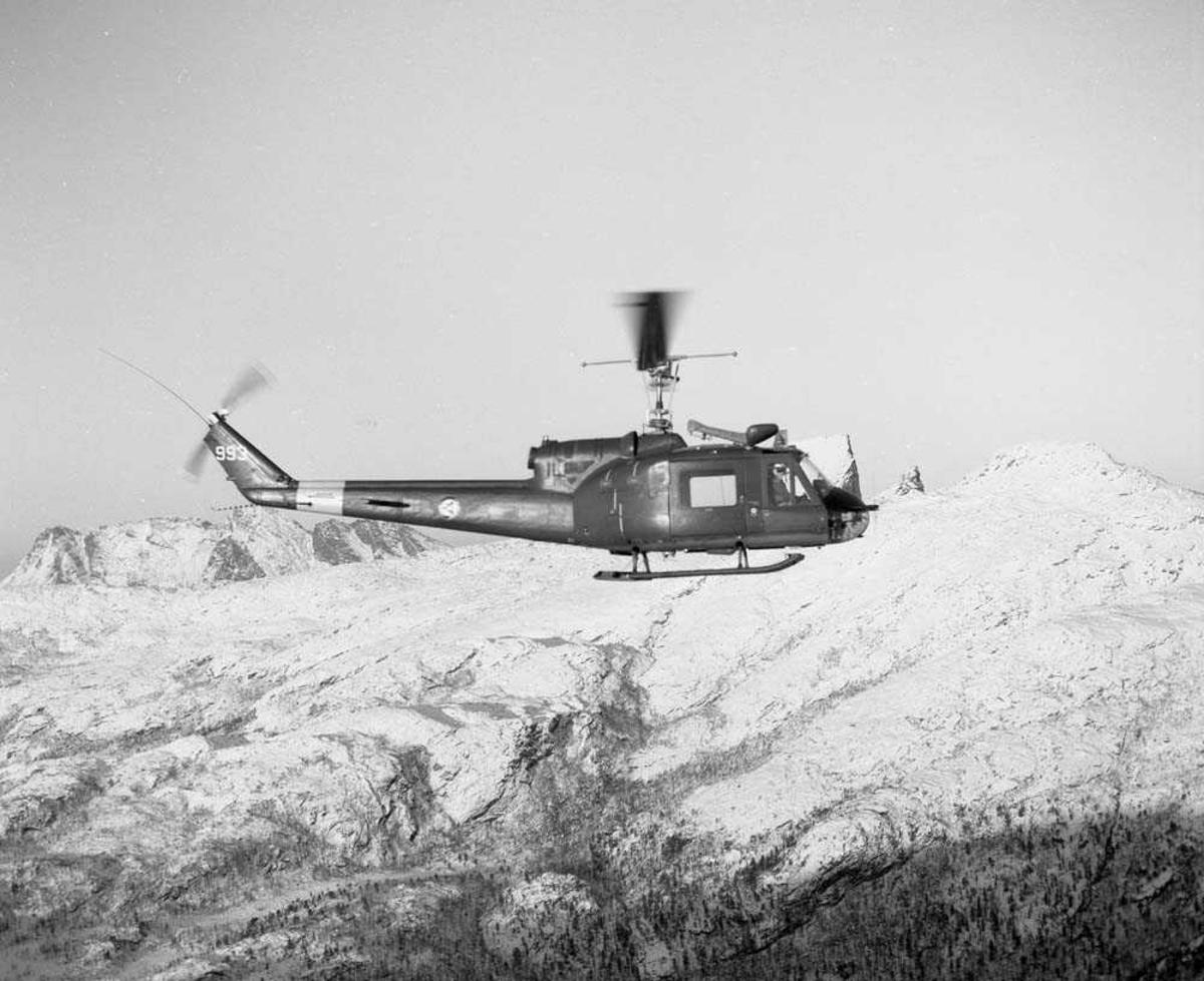 Bell UH-1B helikopter med kjennetegn 993, tilhørende 719 skvadron på Bodø flystasjon, i luften noen mil nord for Bodø. I bakgrunnen sees Steigtind.